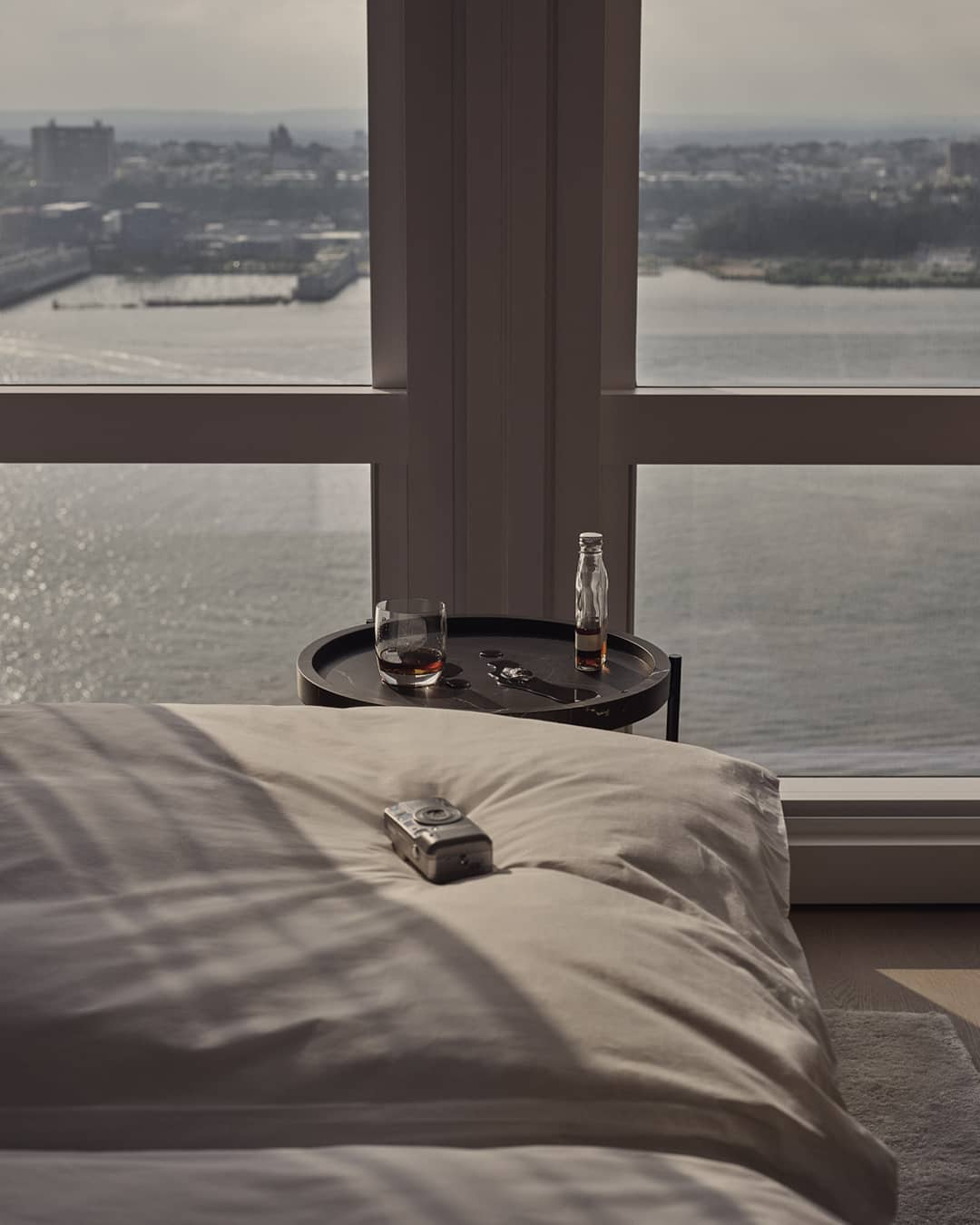 equinox hotel room closeup of bed in front of floor to ceiling windows showing river view