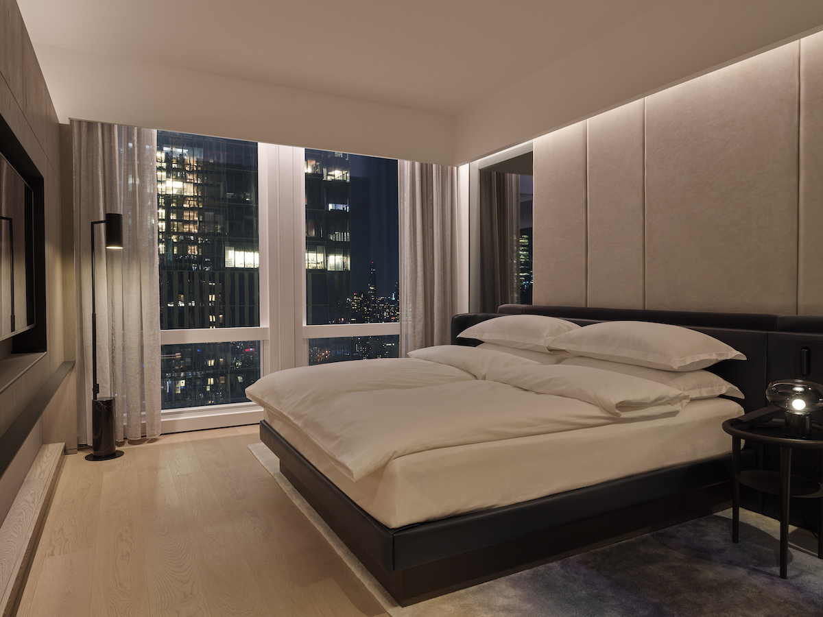 equinox hotel room king bed with city skyline seen through window