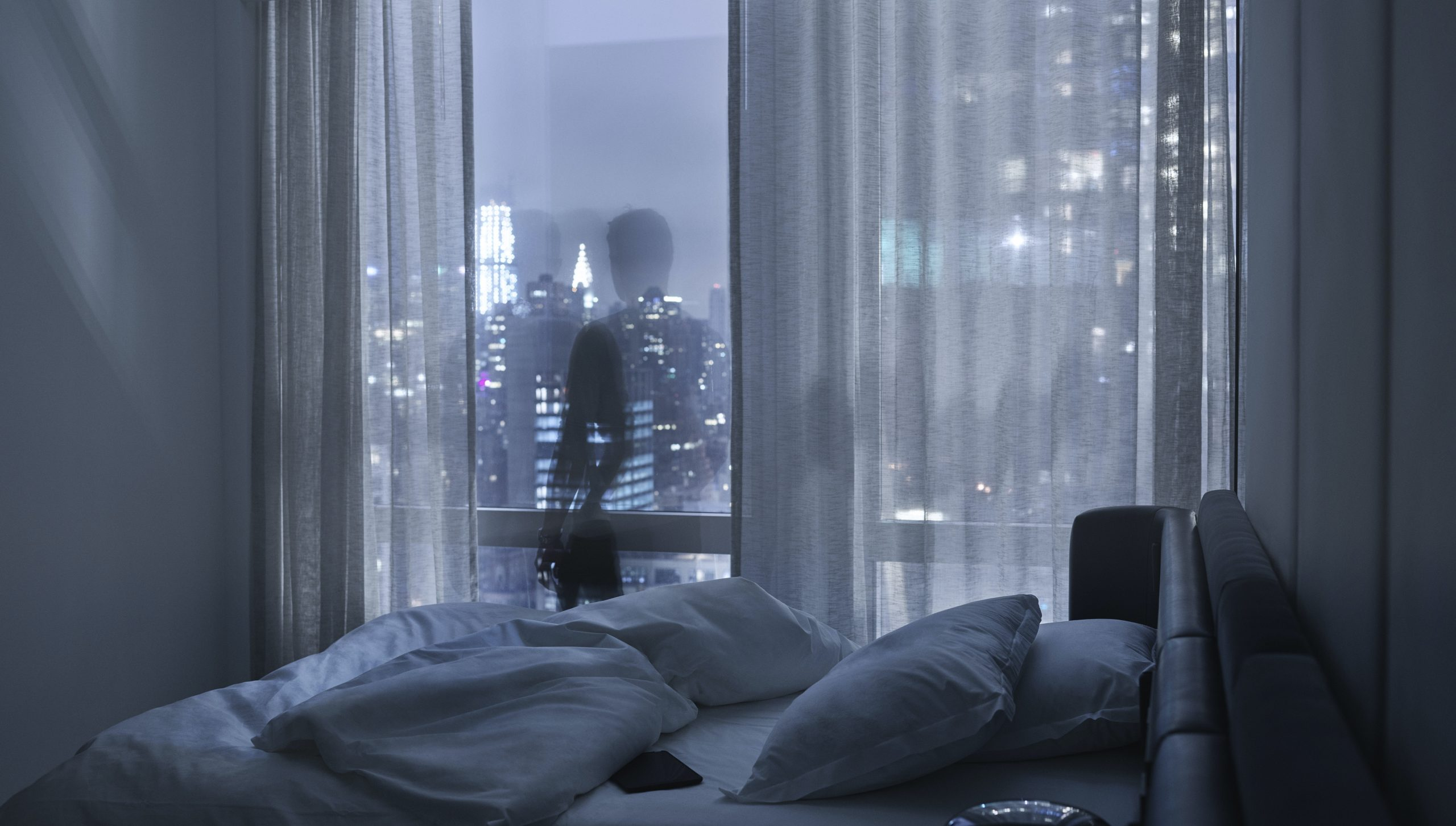 silhouette of man in front of window in guest room at night with city skyline lights in distance and bed in foreground