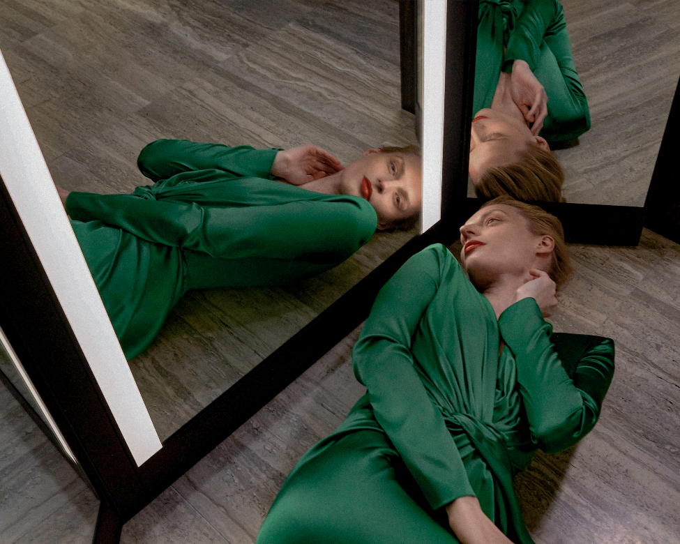 woman laying on floor in front of triptych mirror