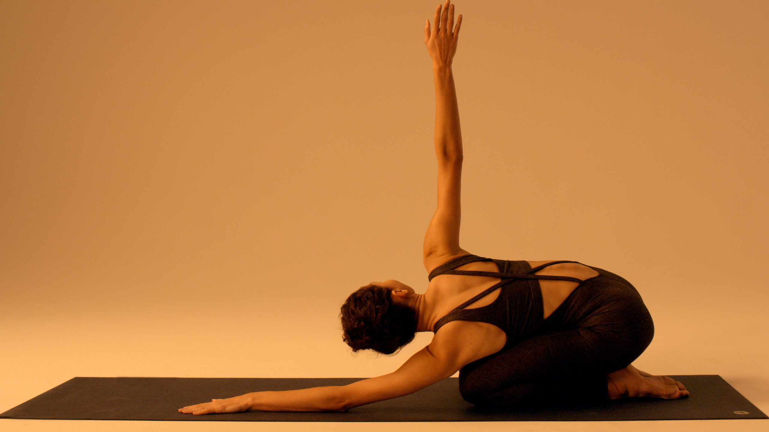 woman in kneeling yoga pose stretching arm up to the sky in twisted position