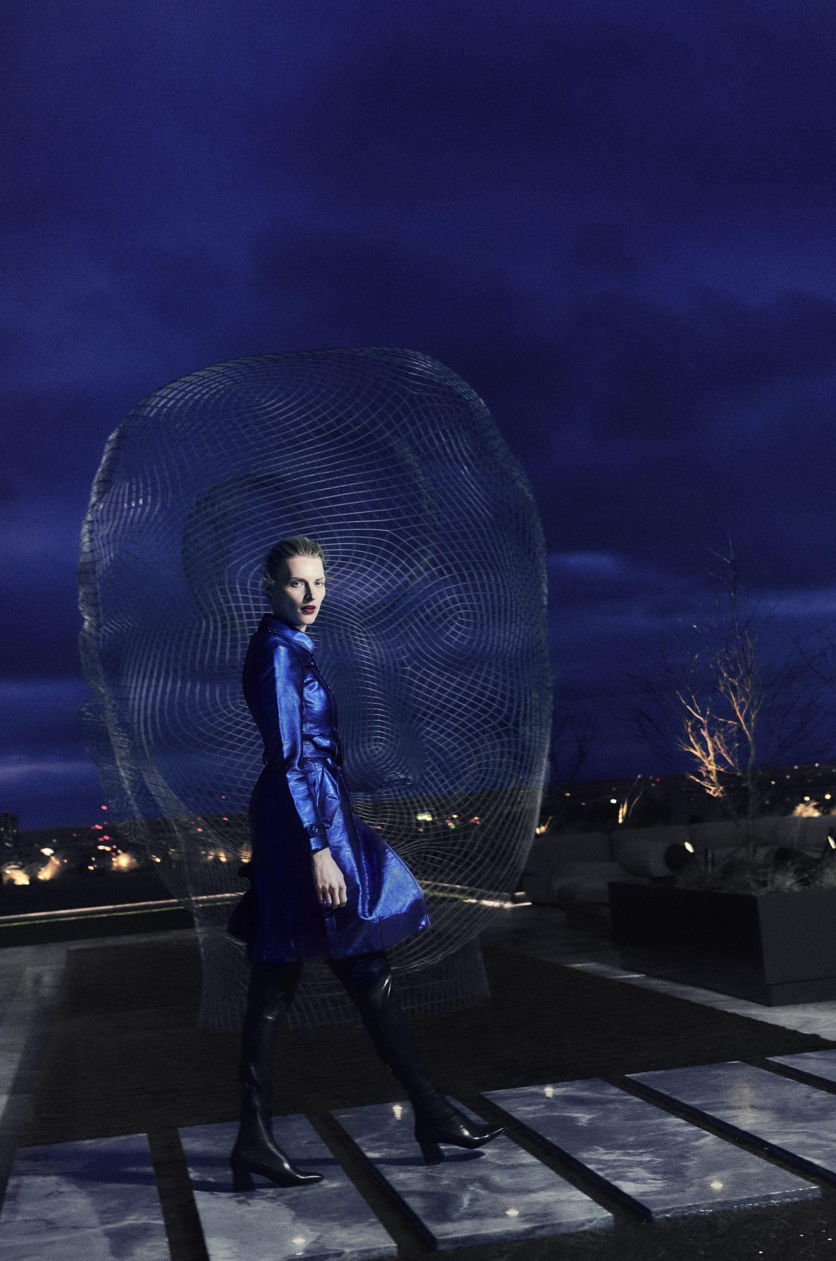 woman walking in front of head sculpture on electric lemon rooftop terrace