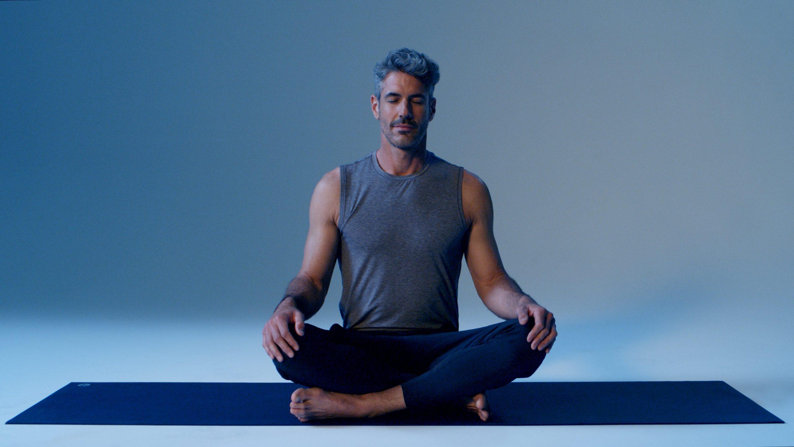 man in seated yoga pose meditating