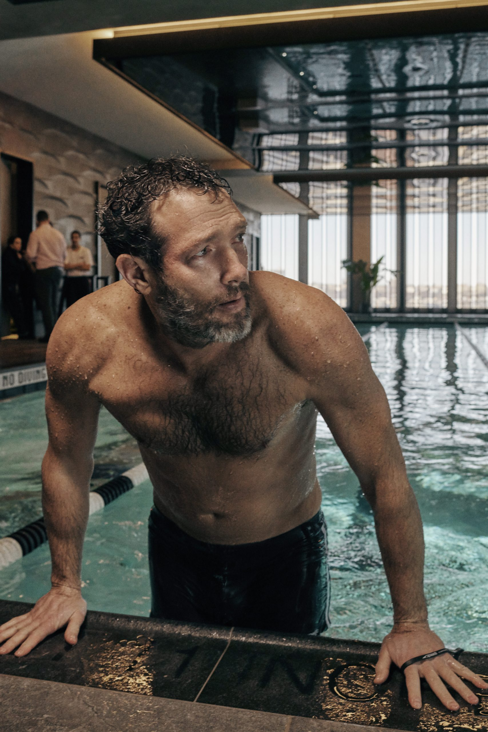 <man getting out of indoor pool at fitness club