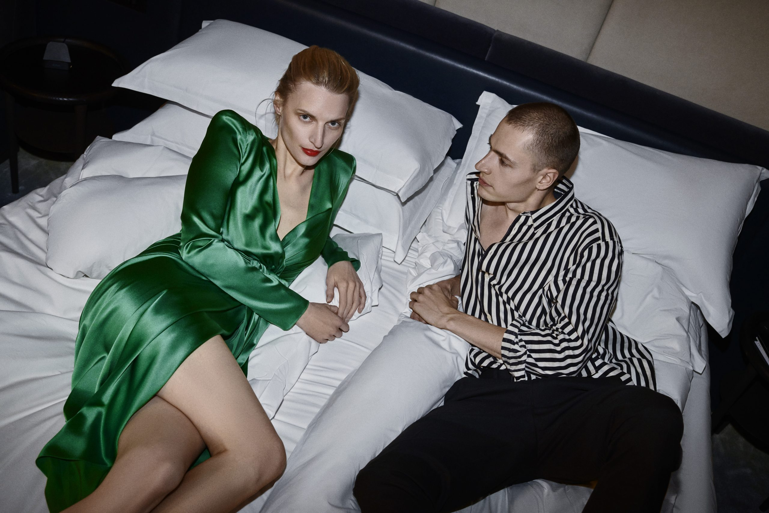 couple in bed wearing fancy outfits after a night out