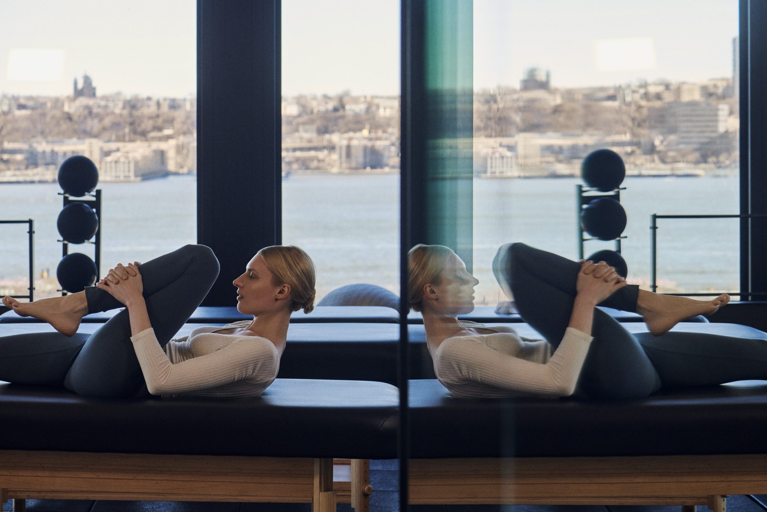<woman stretching on table in fitness club with hudson river seen through windows in background