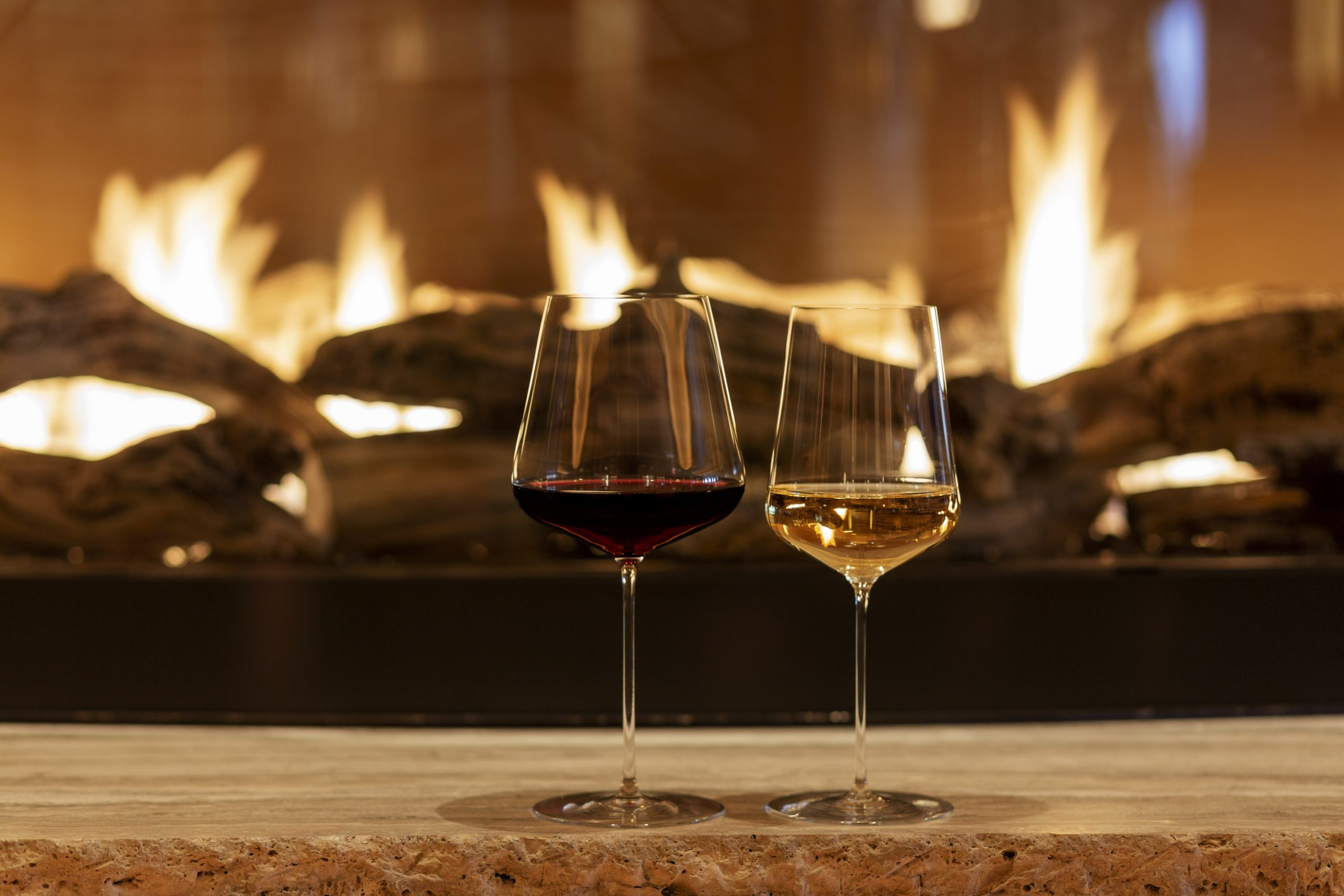 <glass of red and white wine in front of fireplace at ws new york