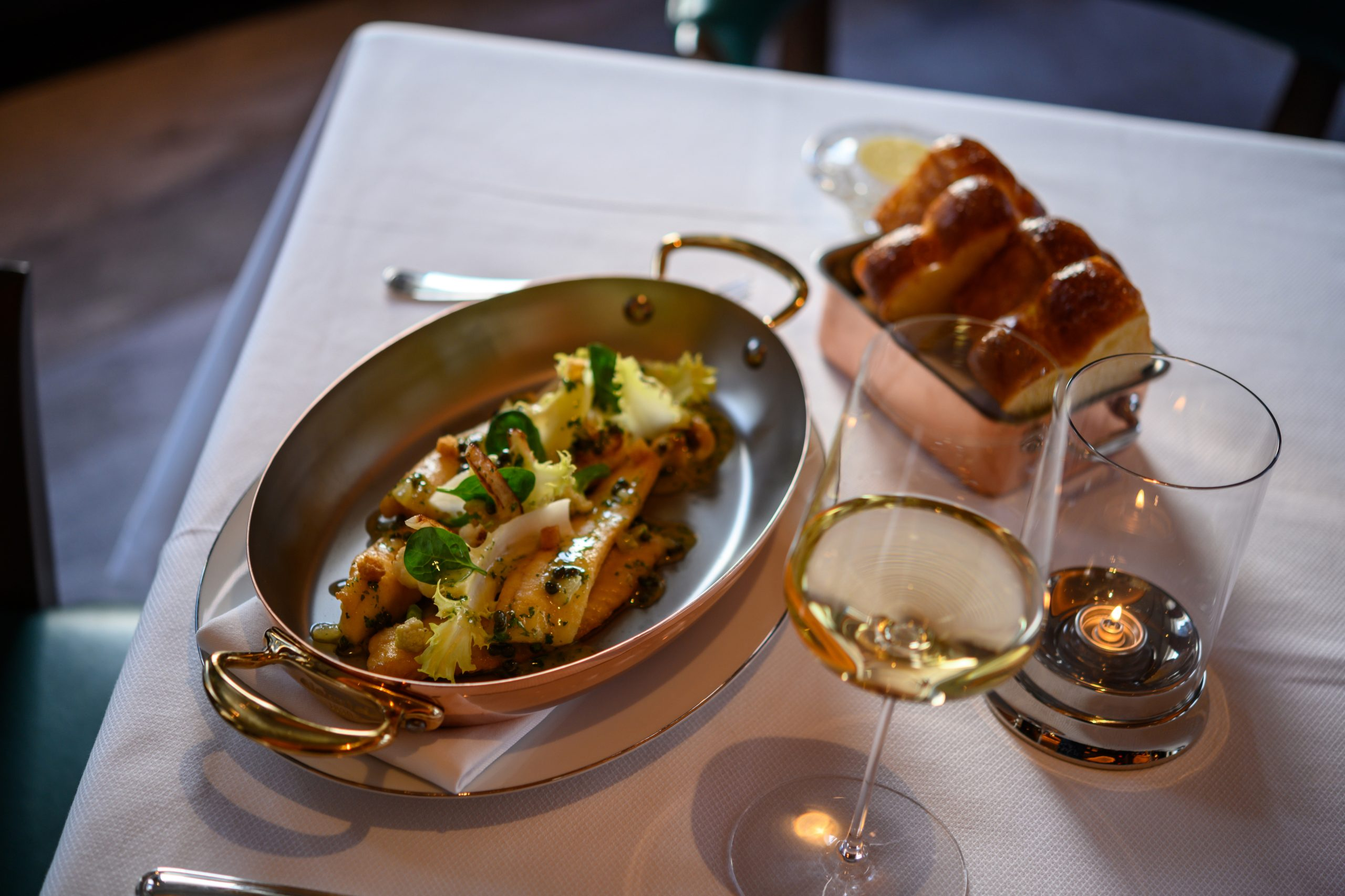 <fish and bread in copper dishes and glass of white wine at ws new york