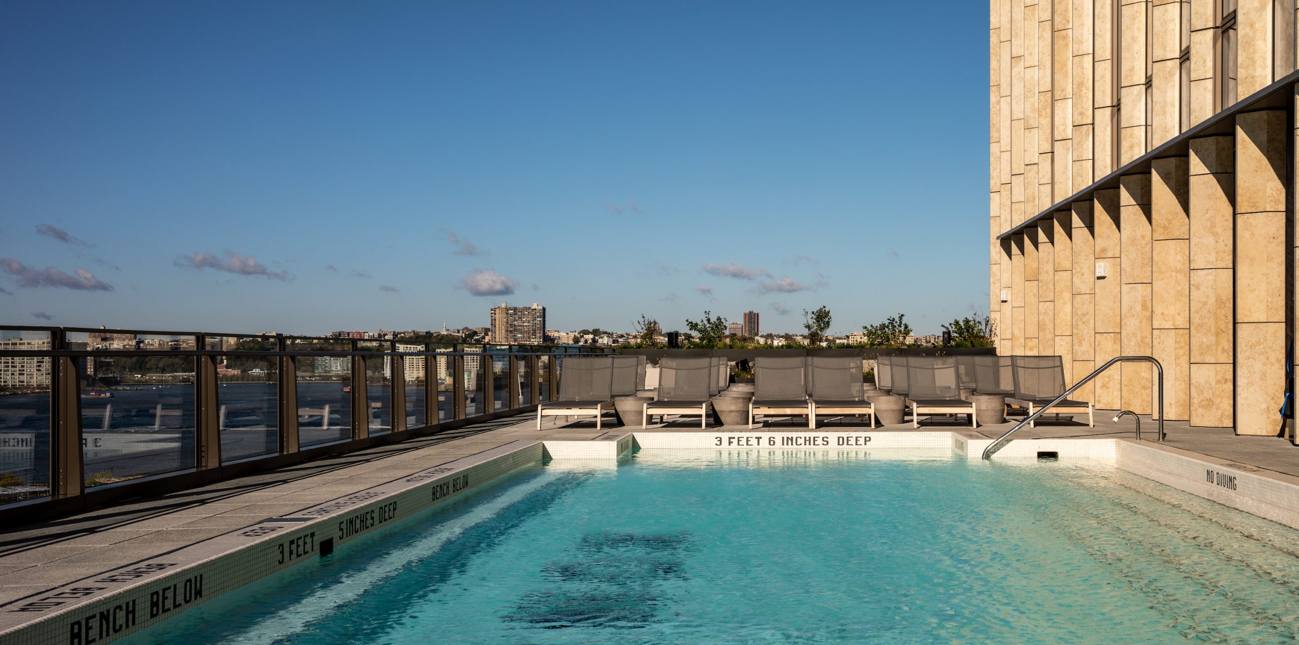 <outdoor pool and sundeck overlooking hudson river