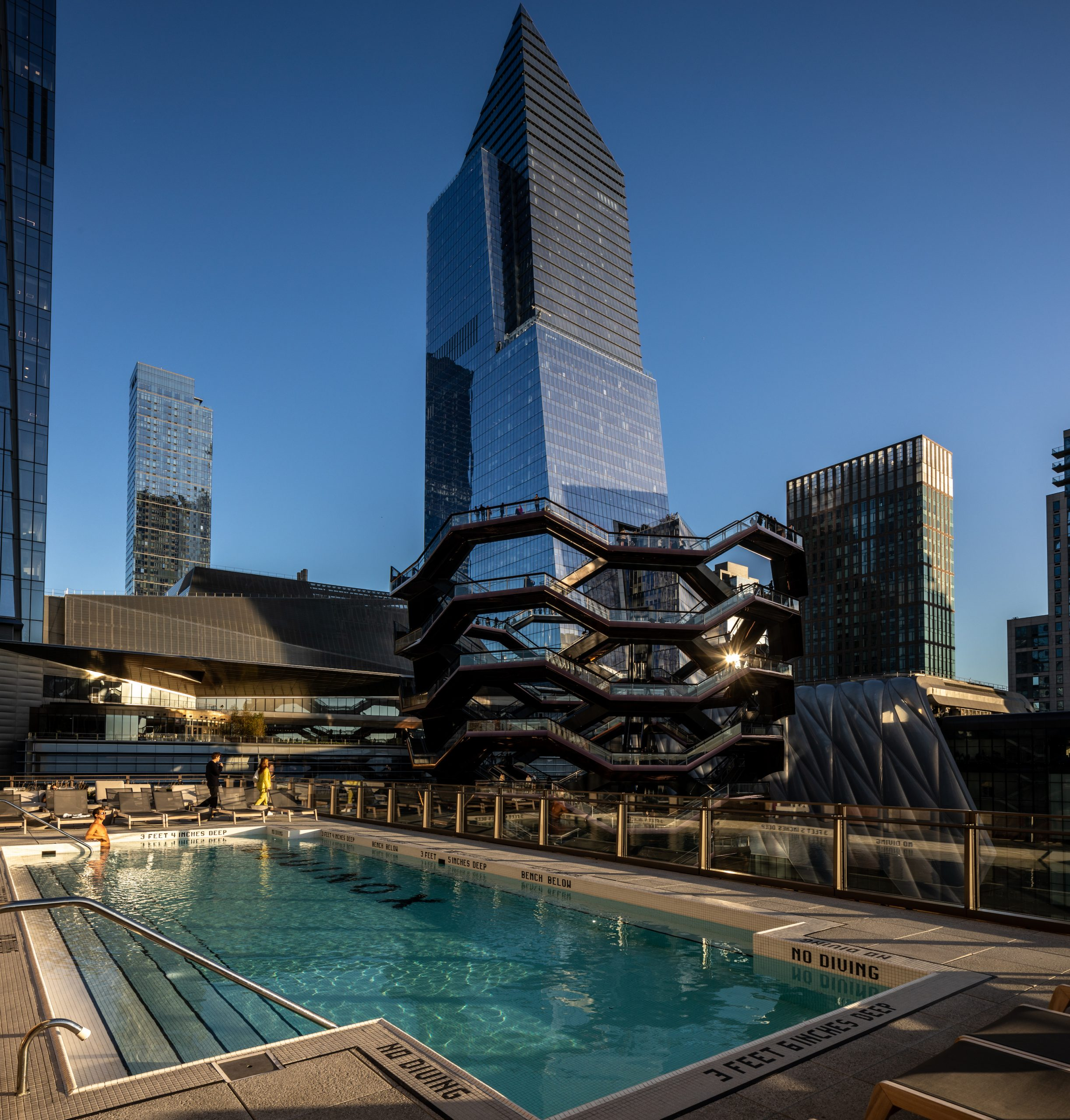 <man in outdoor pool overlooking hudson yards plaza and vessel with view of skyscrapers