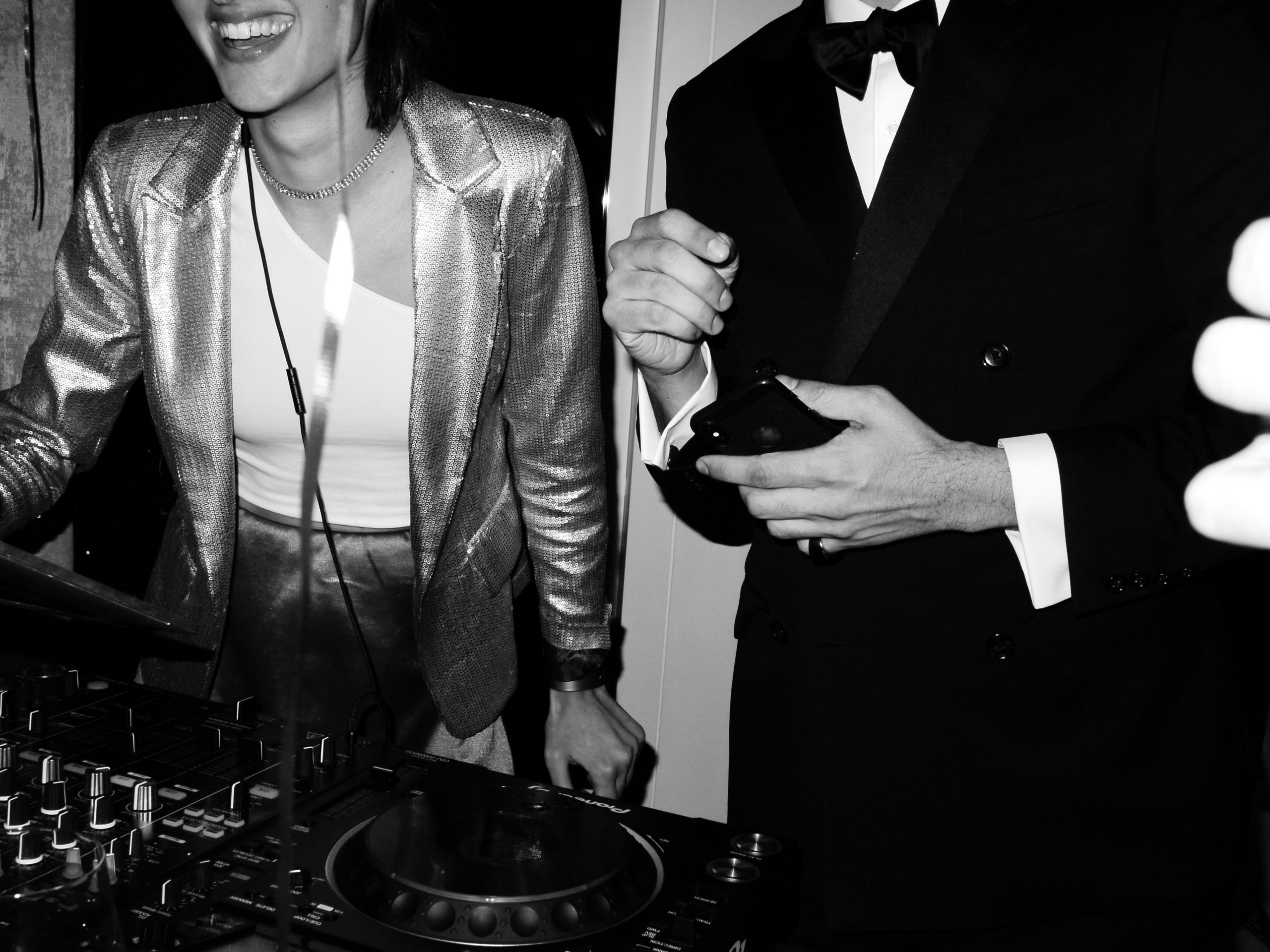 female dj smiling with man in tuxedo at party