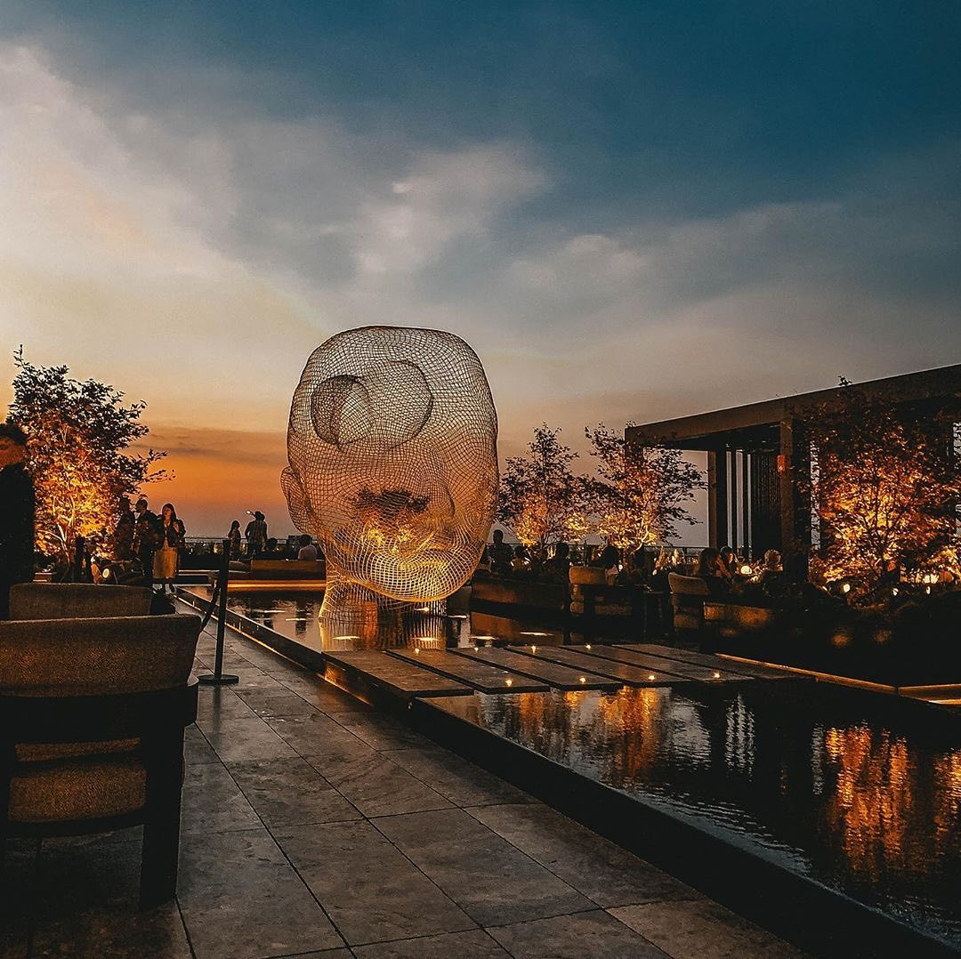view of woman's head sculpture on electric lemon restaurant rooftop terrace with trees lit up and sunset in background