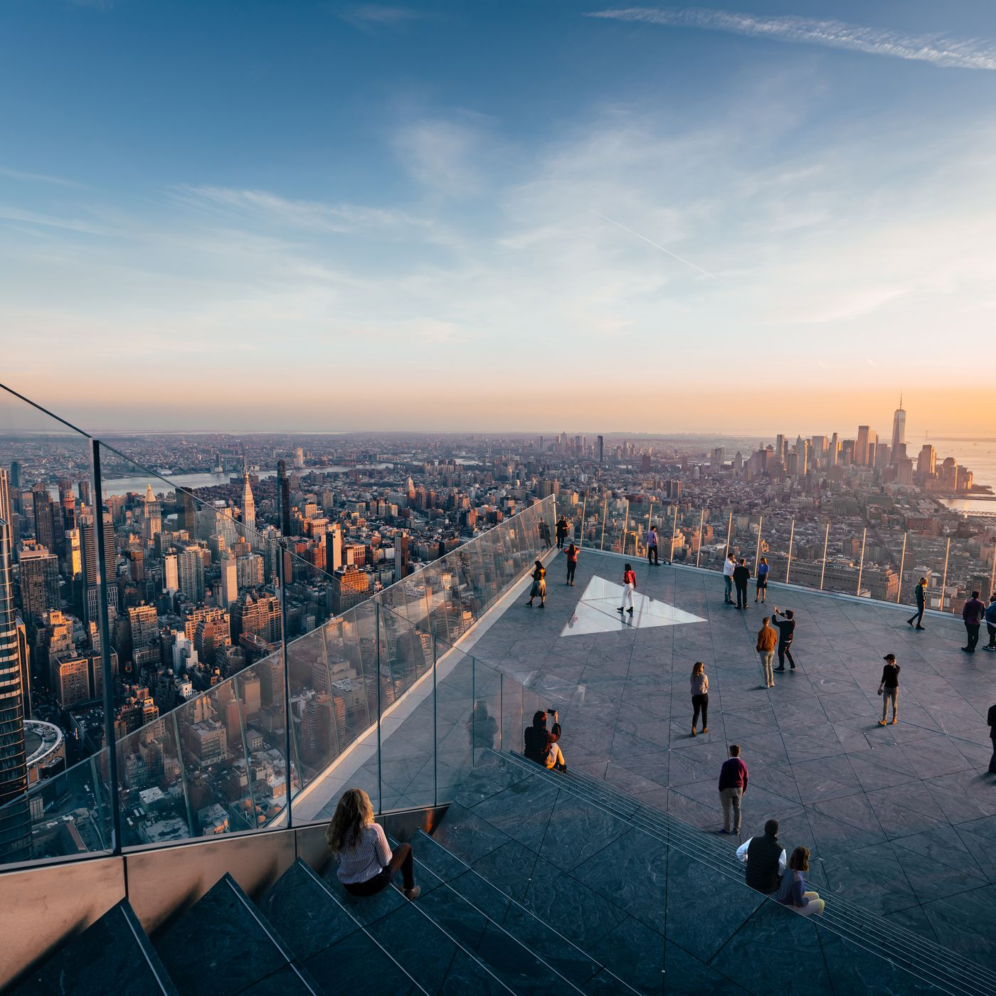 visitors on edge observation deck overlooking nyc skyline
