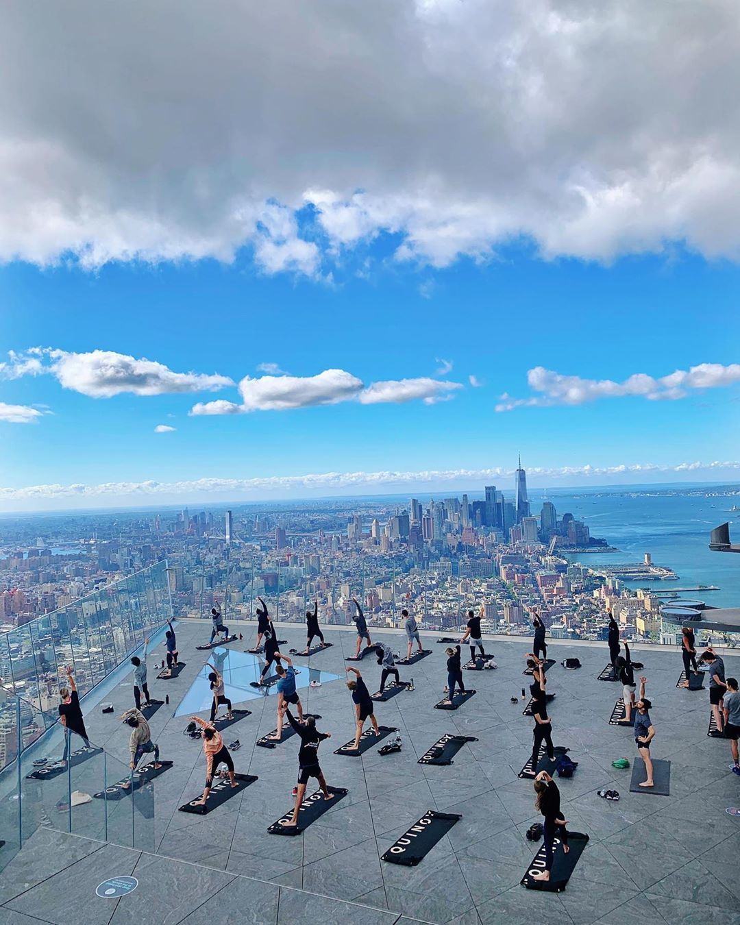 <yoga group fitness class on edge observation deck with view overlooking city to downtown manhattan
