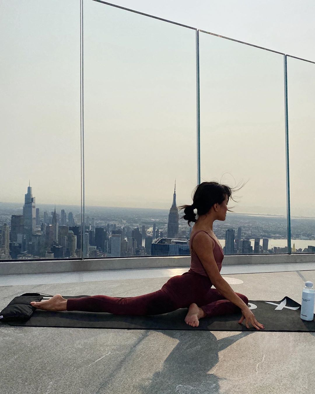 <woman in pigeon yoga position on edge observation deck with view of empire state building and nyc skyline in background