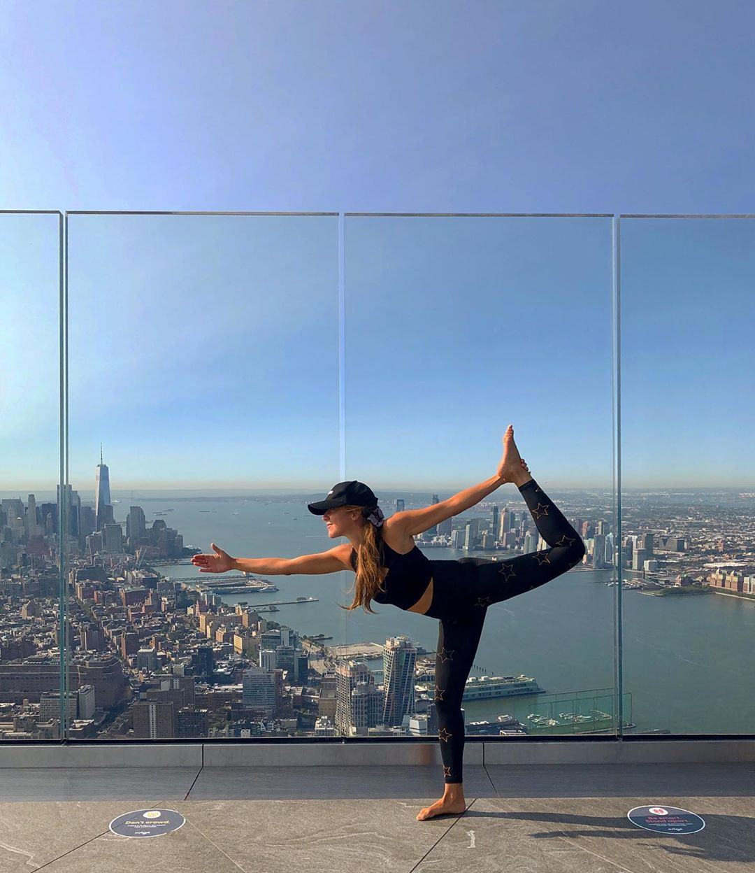 <woman doing yoga pose on edge observation deck with hudson river and nyc skyline in background