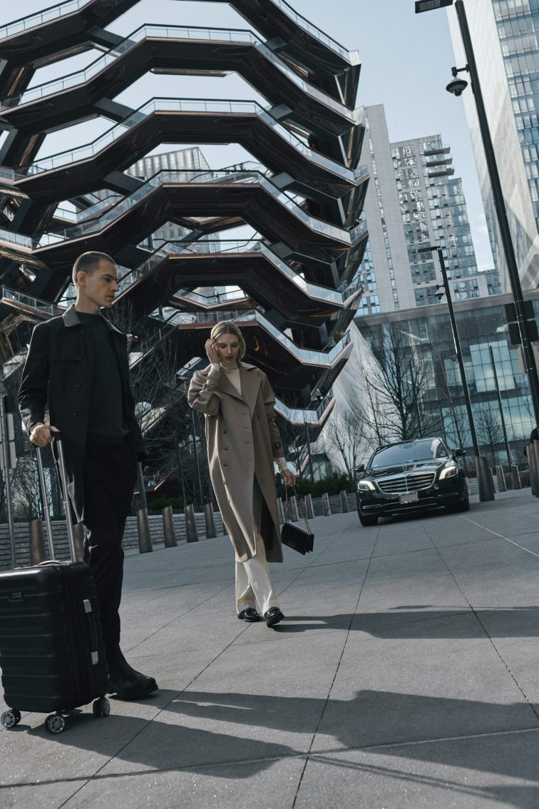 couple arriving at private driveway entrance of equinox hotel new york with vessel in background