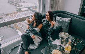 two women on couch with champagne