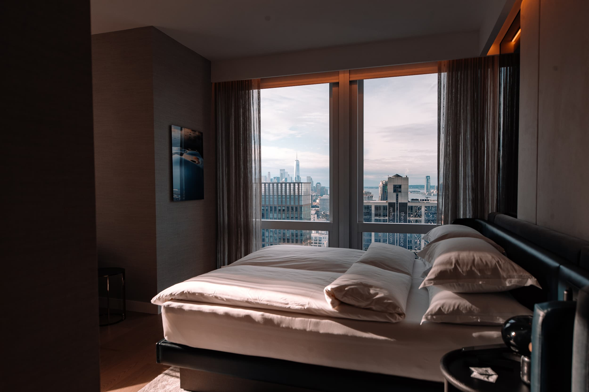 <hotel bed with view to downtown manhattan freedom tower