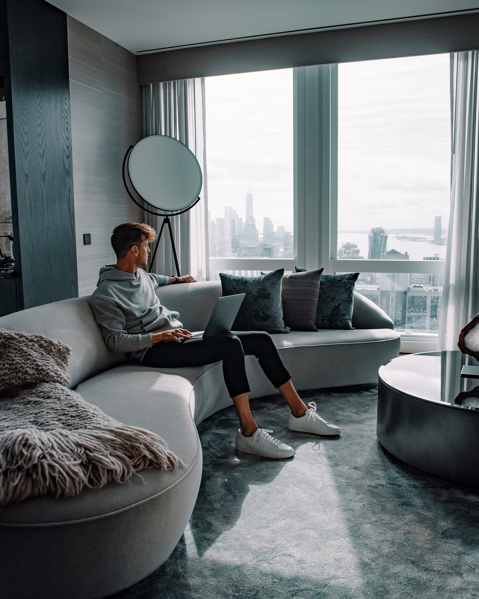 <man sitting with laptop on couch with view downtown