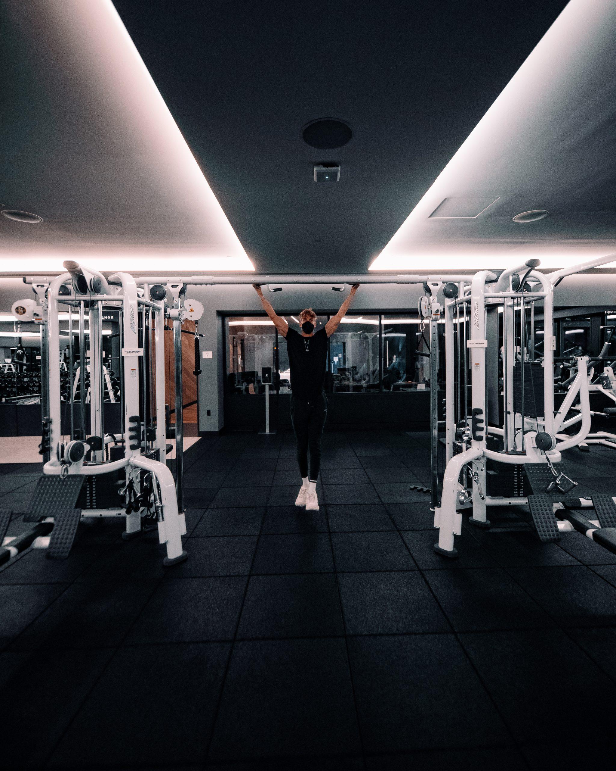 man doing pull ups in equinox fitness club