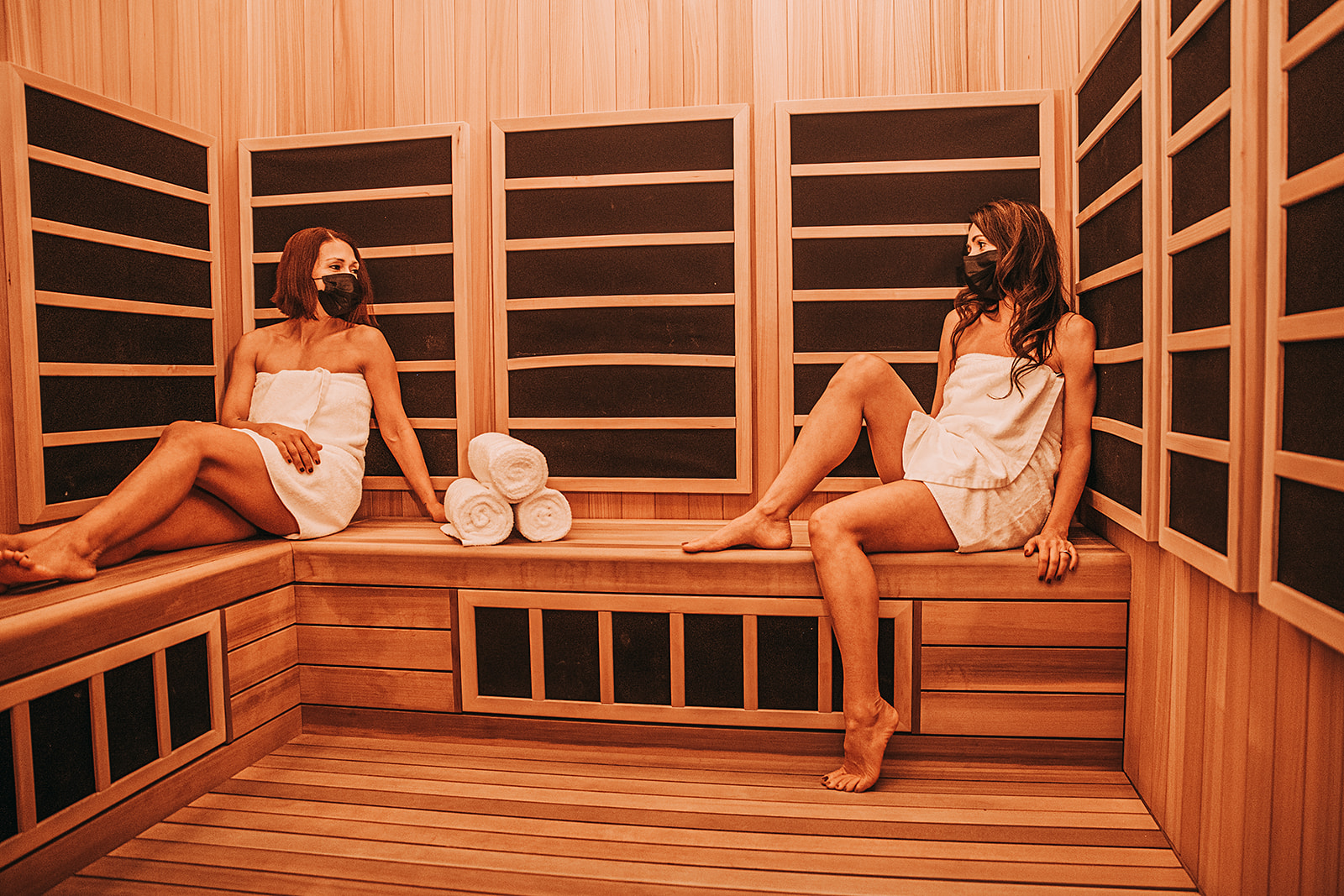 two women in infrared sauna wearing masks