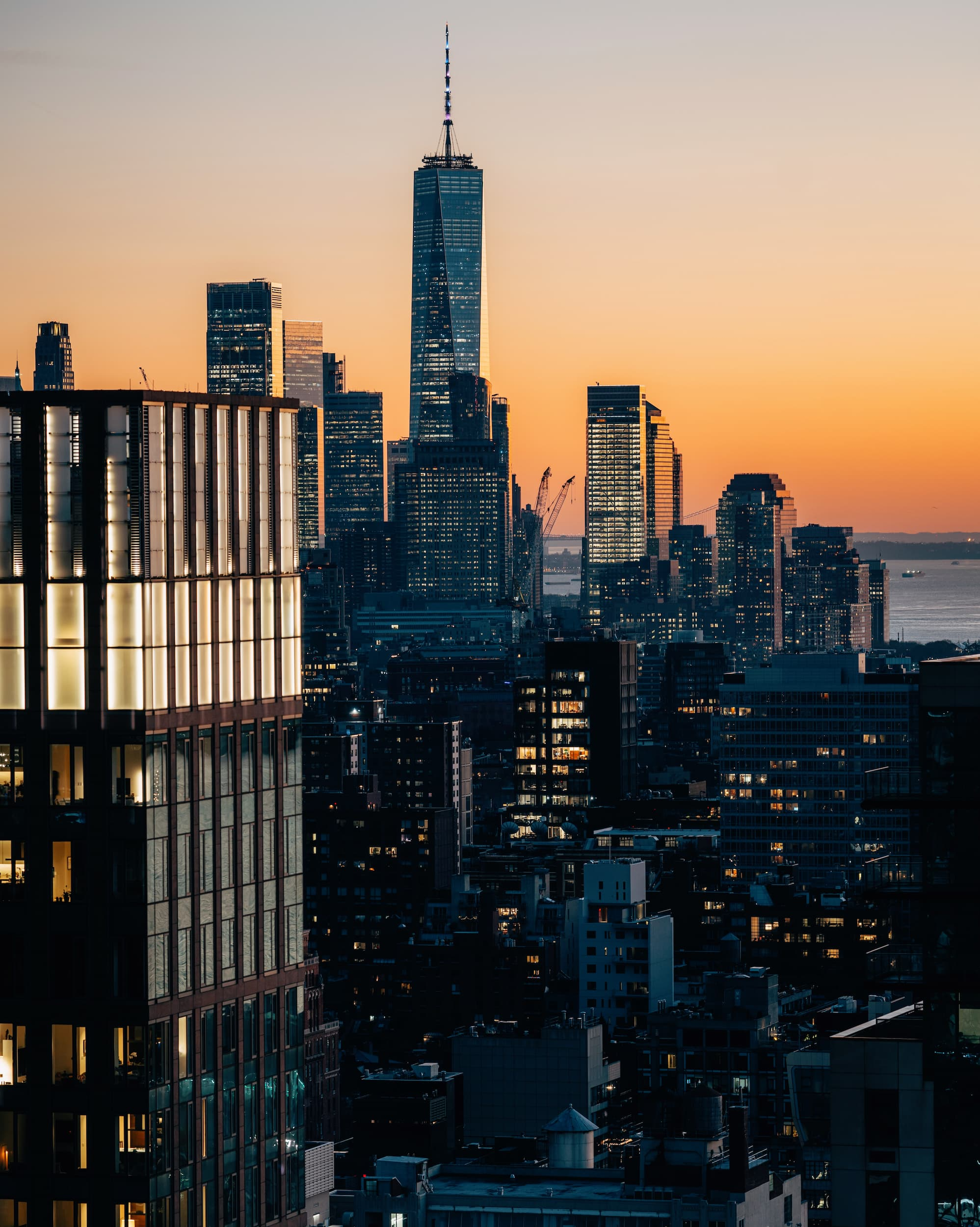 view of city skyline with freedom tower at sunset