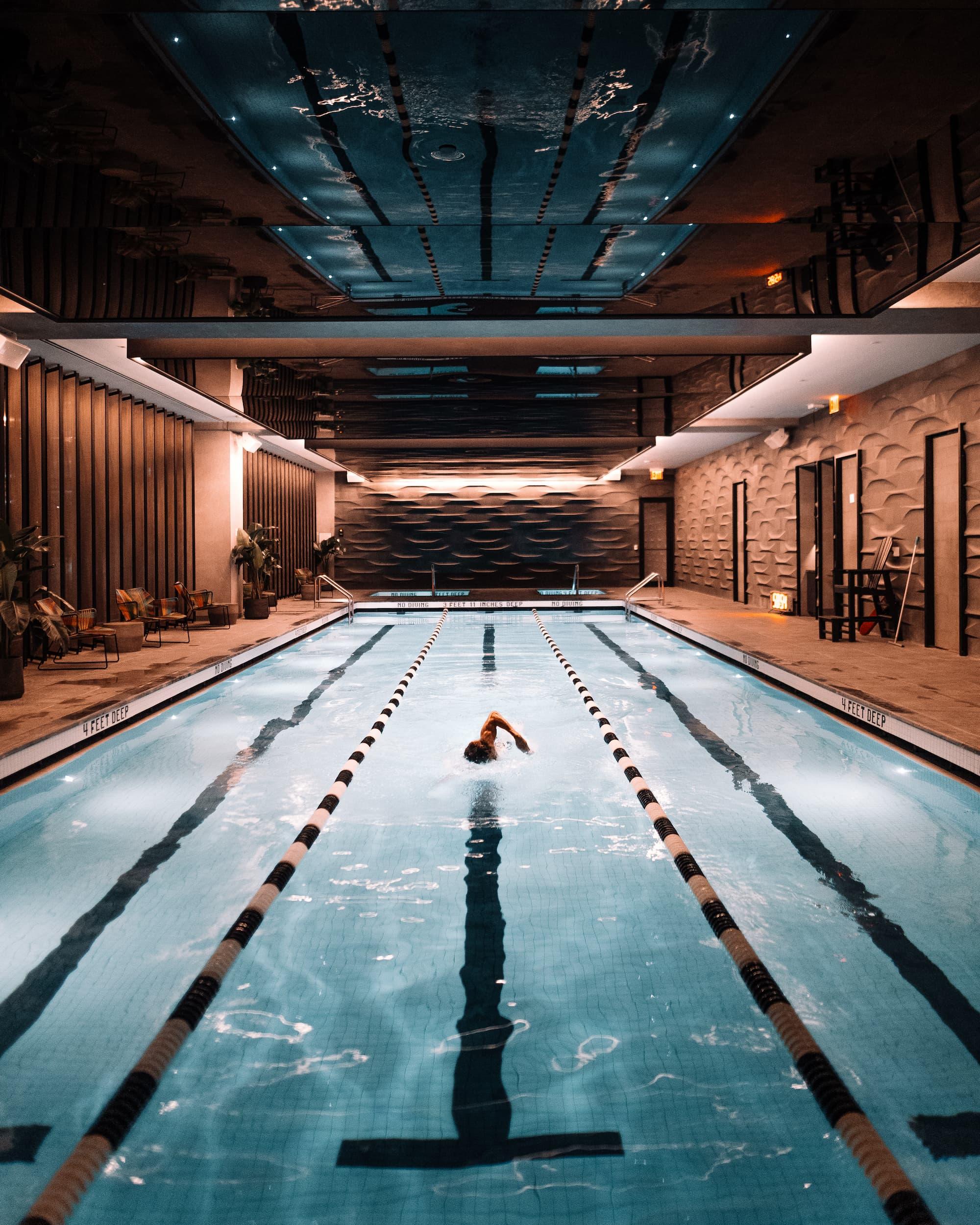 man swimming laps in indoor pool