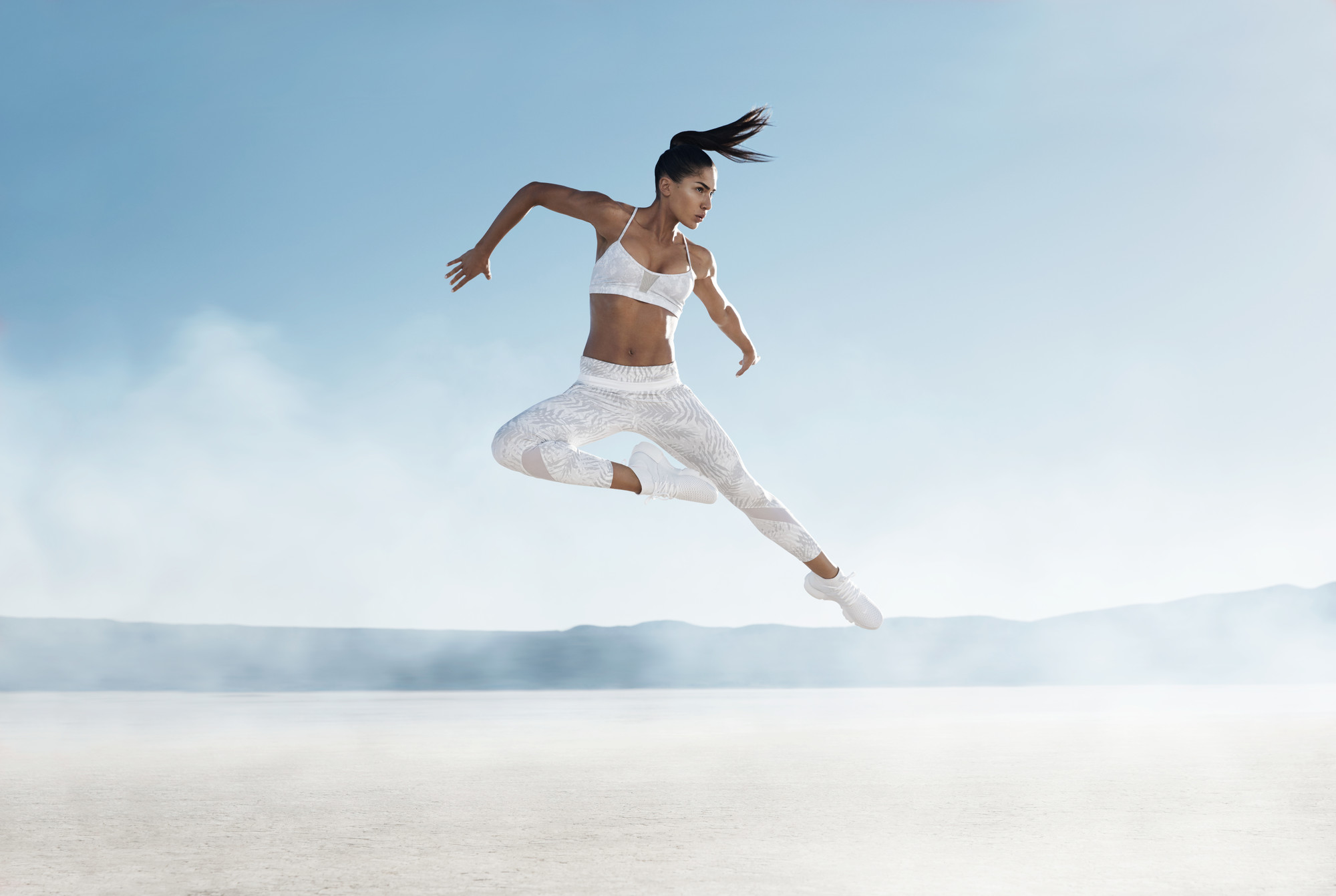 girl jumping in air in desert in workout gear