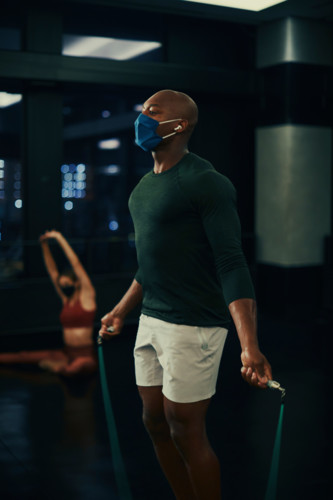 man jumping rope in mask in fitness center